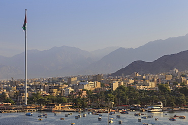 Elevated view of Aqaba seafront with huge Jordanian flag, boats and hazy mountains in distance, Aqaba, Jordan, Middle East
