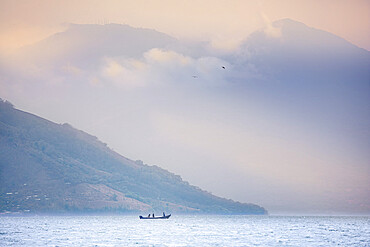 Fishing boat against the looming backdrop of Conchagua Volcano and the Cerro Cacahuatique, Gulf of Fonseca, El Salvador, Central America