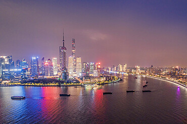 The illuminated skyline of Pudong district in Shanghai with the Huangpu River in the foreground, Shanghai, China, Asia