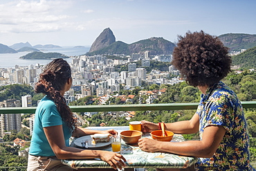 A multi-ethnic couple breakfasting together and looking out over Sugar Loaf mountain and the Rio skyline, Rio de Janeiro, Brazil, South America