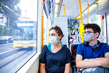 A mother and son wearing health protection masks on a public tram (trolley car), Lisbon, Portugal, Europe
