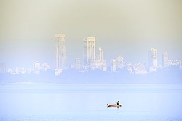 A fisherman in front of the skyscrapers of the Malabar Hills in Mumbai (Bombay), Maharashtra, India, Asia