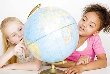 Multi-ethnic girls looking at globe