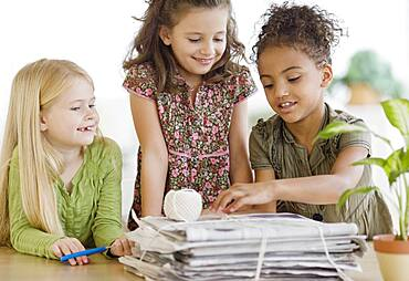Multi-ethnic girls bundling newspapers