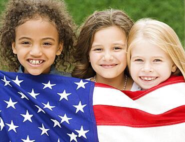 Multi-ethnic girls holding American flag