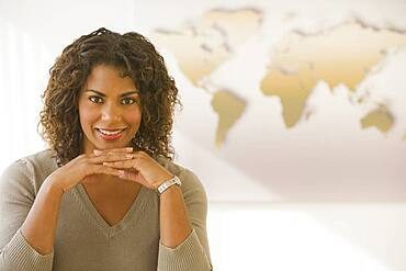 African businesswoman in front of world map