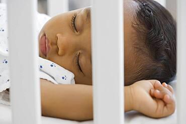 African American baby sleeping in crib