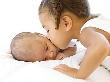African girl kissing newborn baby sibling