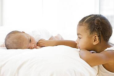 African girl looking at baby sibling