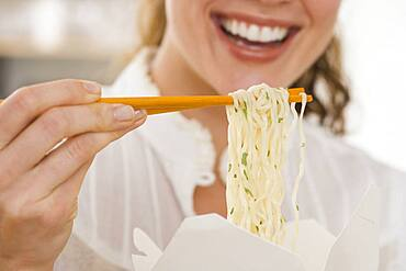 Close up of woman eating noodles with chopsticks