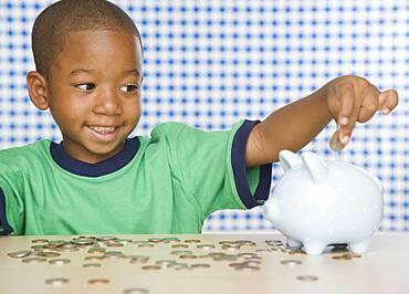 African boy putting change in piggy bank