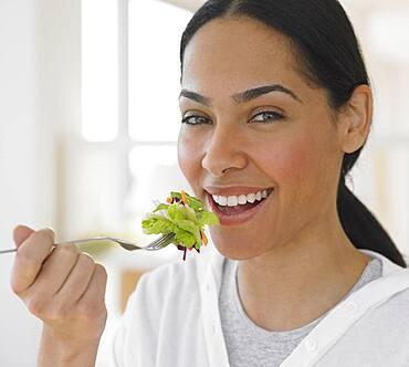African woman eating salad