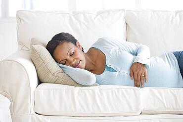 Pregnant African woman sleeping on sofa