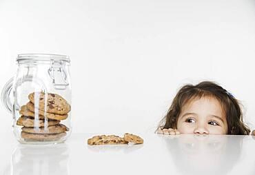 Little girl looking at cookie jar