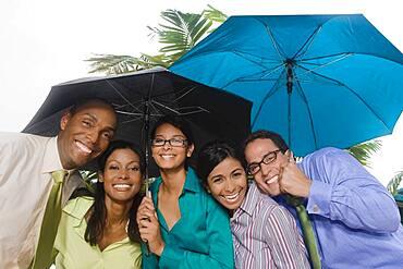 Hispanic businesspeople standing under umbrellas