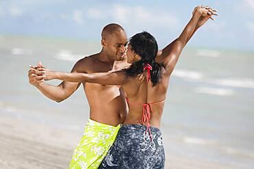 Multi-ethnic couple dancing at beach