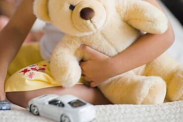 African girl holding teddy bear