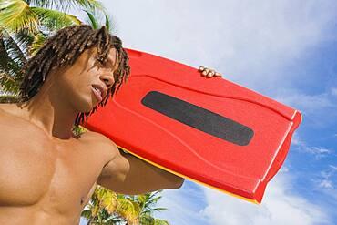 African man carrying lifeguard float