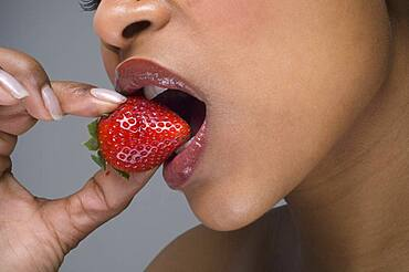 African woman eating strawberry