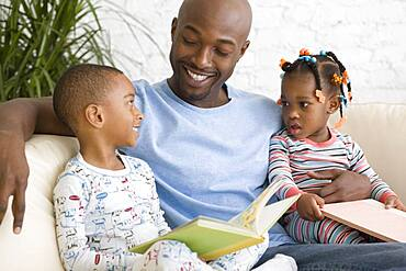 African father reading to children