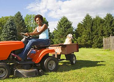 African American woman mowing lawn