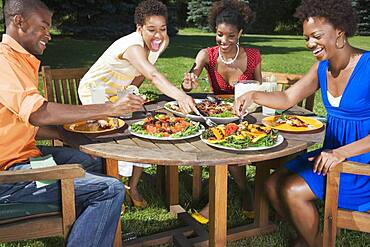 African American friends eating outdoors