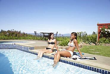 Multi-ethnic women with feet in swimming pool