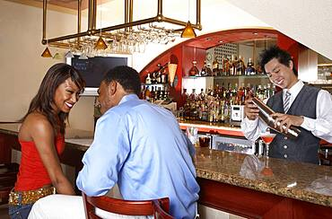 African American couple sitting at bar