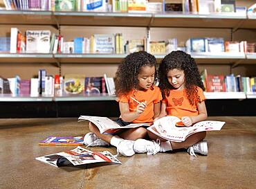 Two young sisters reading books in library