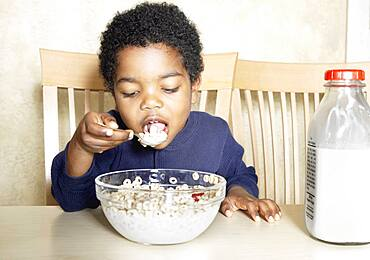 Young African American boy eating cereal
