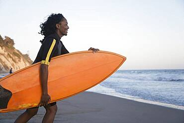 African woman carrying surfboard