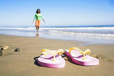 Flip-flops on beach in front of woman