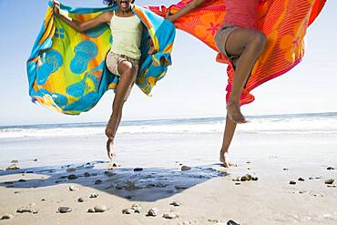 African sisters running with beach towels