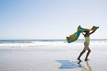 African girl holding beach towel in wind