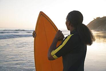 Mixed Race woman holding surfboard
