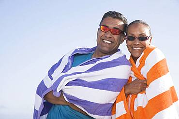 Multi-ethnic couple wrapped in beach towels