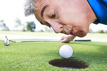 Man blowing on golf ball