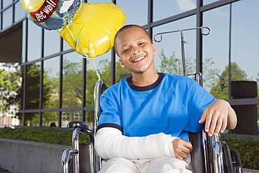 African boy with broken arm and balloons in wheelchair