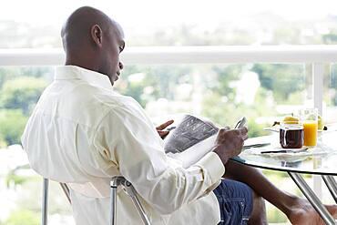 African American man reading magazine
