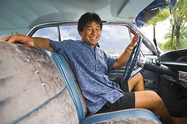 Asian man sitting in car