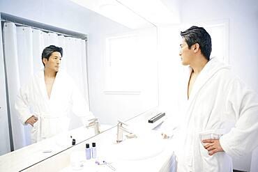 Asian man looking in bathroom mirror