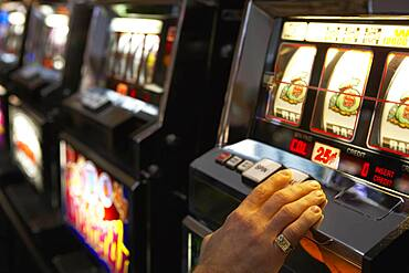 Man pushing the spin button on a slot machine