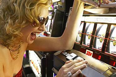 Young woman winning at the slot machine