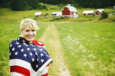 Woman on farm wrapped in American flag