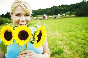 Woman holding sunflowers on farm