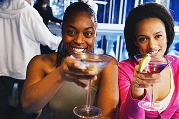 Two African women toasting with cocktails