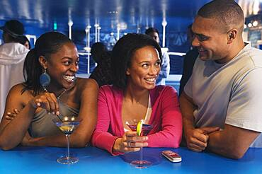 Three African friends laughing at bar