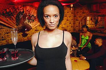 African cocktail waitress holding tray of drinks