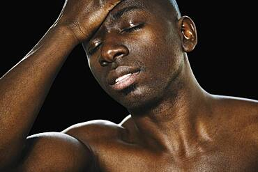 Close up of African man with hand on forehead