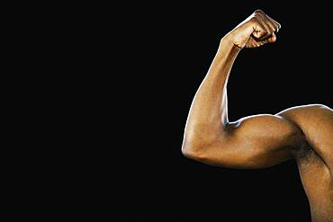 Studio shot of African man flexing biceps